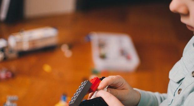 bambino che gioca con mattoncini della Lego