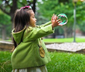 bambina al parco che gioca con le bolle di sapone