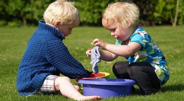 due bambini biondi che giocano in un prato