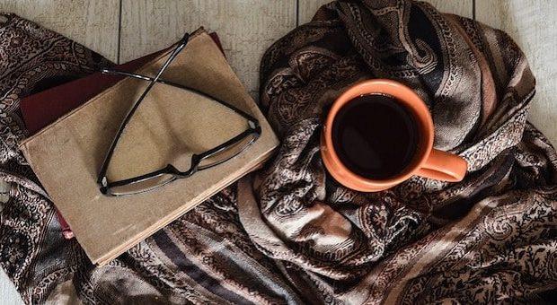 tazzine di caffè e occhiali su un libro chiuso