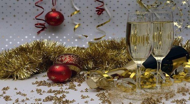 addobbi natalizi dorati e due bicchieri di spumante