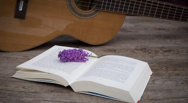 libro aperto con fiori di lavanda e una chitarra