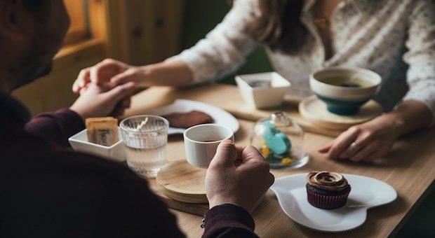 innamorati al bar con caffè e pasticcini