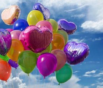 Palloncini colorati a forma di cuore che volano in cielo