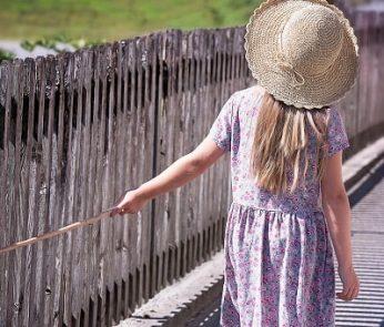 Bambina che passeggia vicino alla staccionata