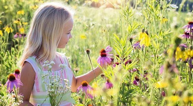 Bambina sul prato fiorito